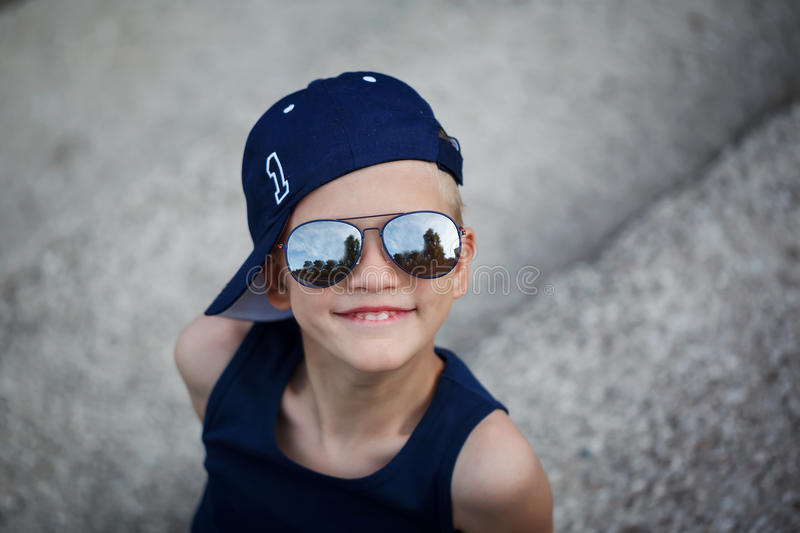 Portrait of Fashionable little boy in sunglasses and cap. Childhood royalty free stock photography