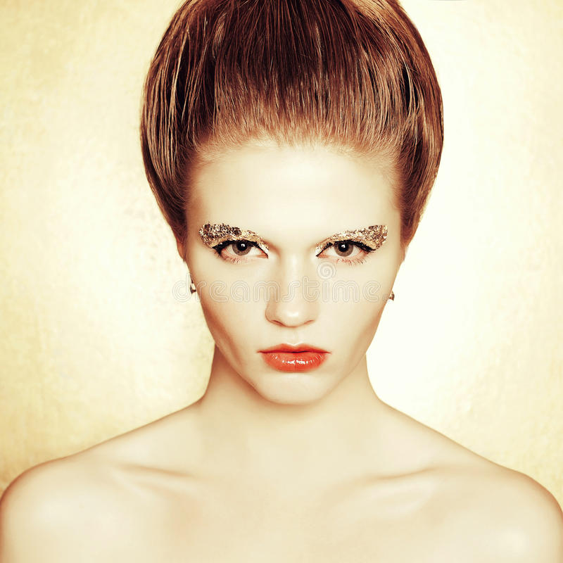 Portrait of fashionable model with retro hairdo, arty make-up royalty free stock images