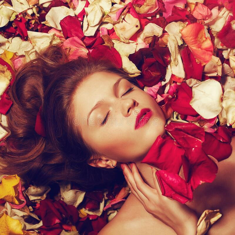 Fashionable red-haired ginger model with sexy red lips lying on fading rose petals background. Studio shot. Portrait of a fashionable red-haired ginger model royalty free stock images