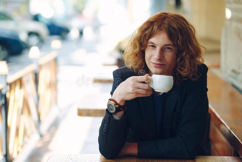 Portrait fashionable reddish man drinking coffee royalty free stock photos