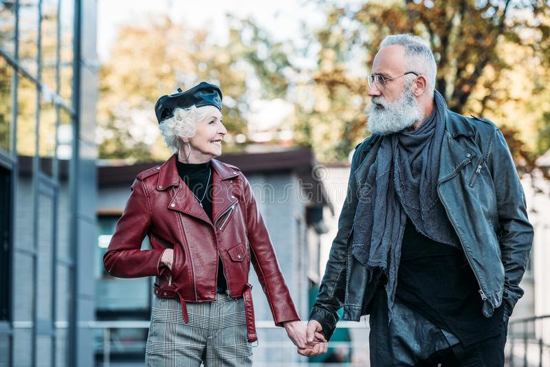 portrait of fashionable senior couple holding hands and looking at each other royalty free stock photo
