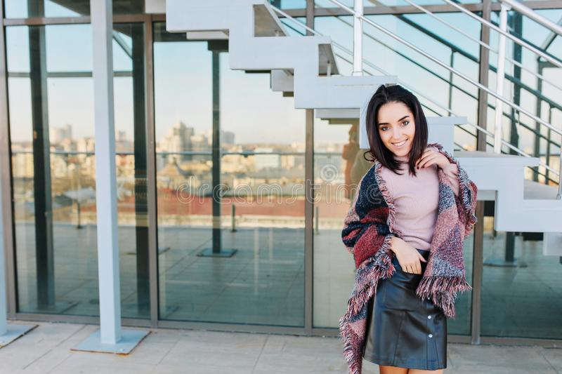 Portrait fashionable smiled young brunette woman on terrace in sunny day on big city view background. Smiling to side stock photos