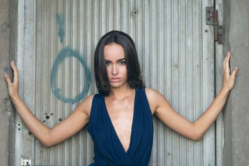 Portrait of a fashionable woman in a blue dress with a neckline. Industrial wall in the background stock images