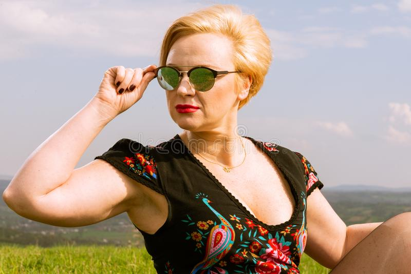Portrait of fashionable woman wearing shades looking far away stock photography