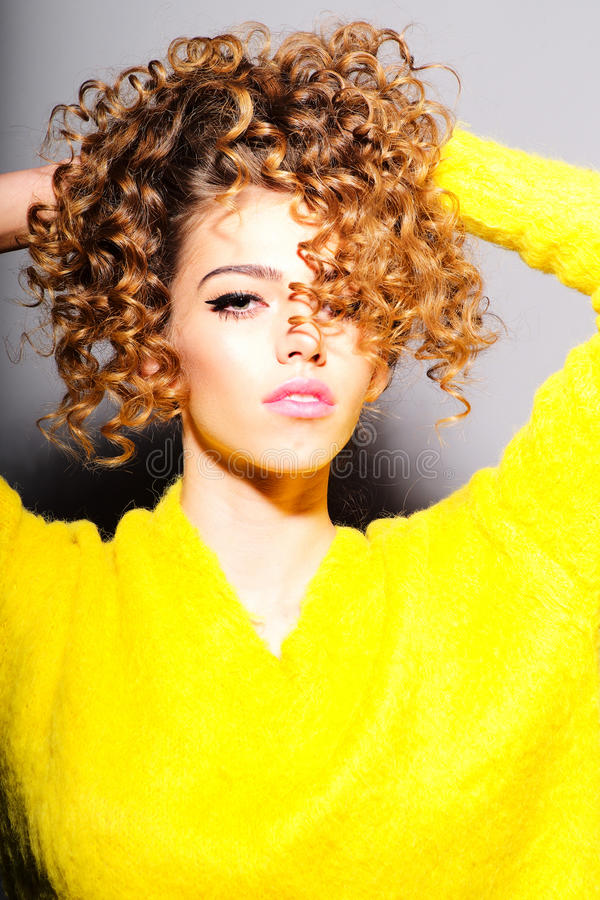 Portrait of fashionable young girl touching her curly hair stock image