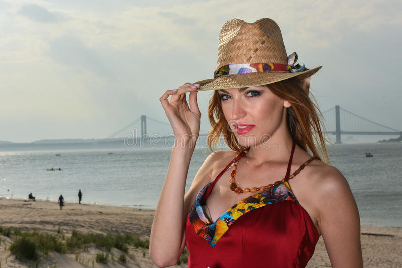 Portrait of fashionable young woman in red dress wearing straw hat stock photo