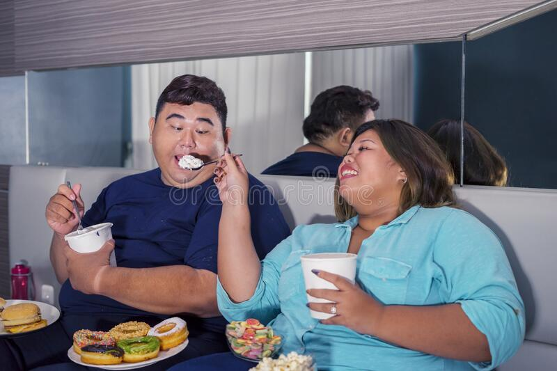 Portrait of fat Asian couple eating ice cream joyfully royalty free stock photo