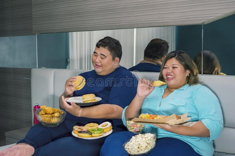 Portrait of fat couple eating burger and pizza stock photo