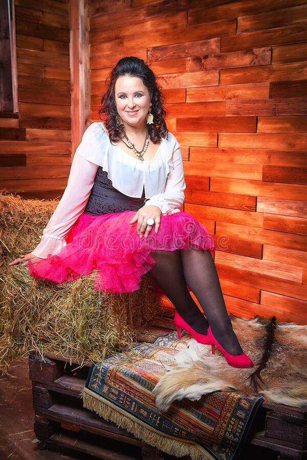 Portrait of fat plump fun charming cute woman with black curly hair in the room with hay and straw royalty free stock photos