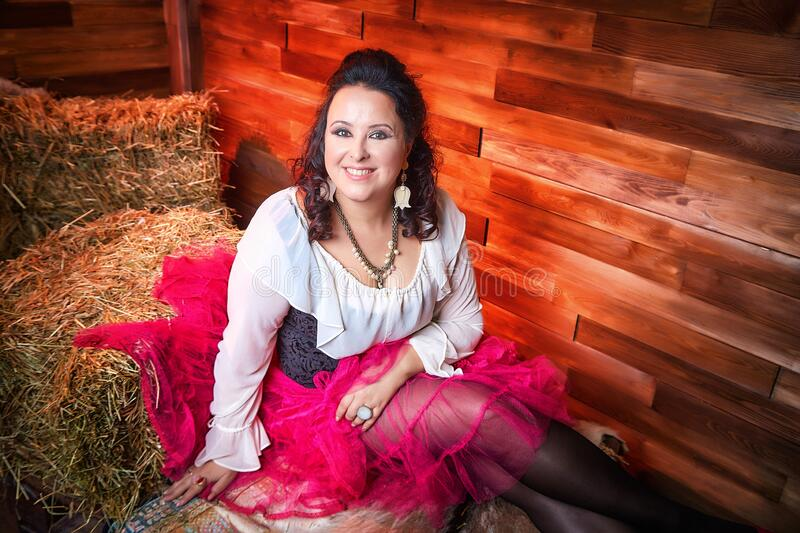 Portrait of fat plump fun charming cute woman with black curly hair in the room with hay and straw stock image