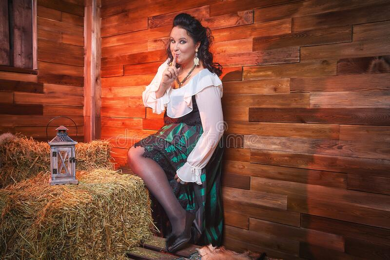 Portrait of fat plump fun charming cute woman with black curly hair in the room with hay and straw stock photography