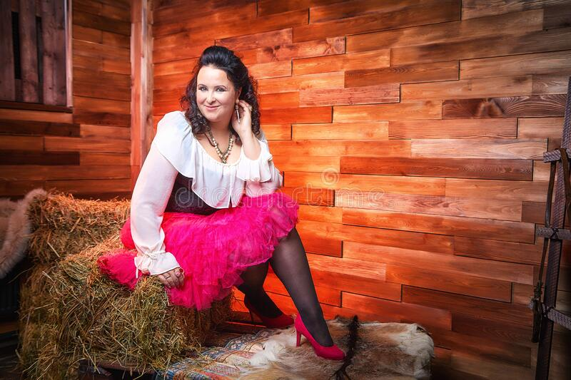 Portrait of fat plump fun charming cute woman with black curly hair in the room with hay and straw. Model posing during photoshoot in studio as like a country royalty free stock photography