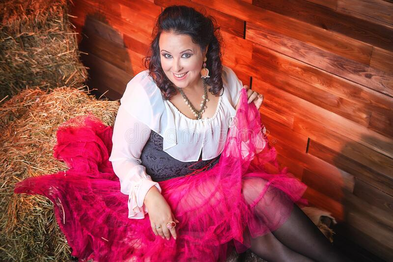 Portrait of fat plump fun charming cute woman with black curly hair in the room with hay and straw. Model posing during photoshoot in studio as like a country stock image
