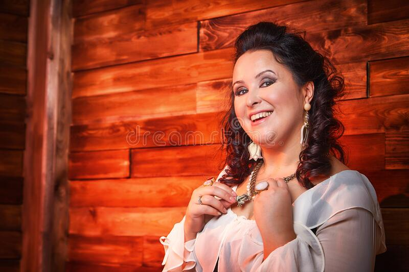 Portrait of fat plump fun charming cute woman with black curly hair in the room with hay and straw. Model posing during photoshoot in studio as like a country royalty free stock photos