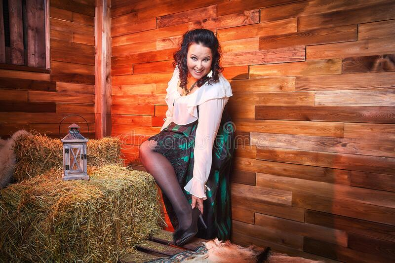 Portrait of fat plump fun charming cute woman with black curly hair in the room with hay and straw. Model posing during photoshoot in studio as like a country stock photos