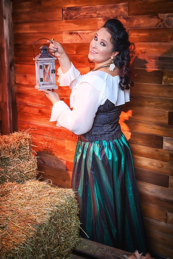 Portrait of fat plump fun charming cute woman with black curly hair in the room with hay and straw. Model posing during photoshoot in studio as like a country royalty free stock image