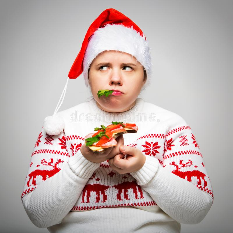 Portrait of a fat woman with a large sandwich in her hands. She is wearing a festive Christmas sweater and Santa hat royalty free stock photos