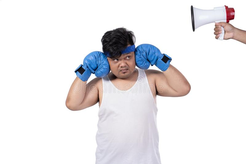 Portrait of fat young man close his ears by hands with boxing gloves royalty free stock photography