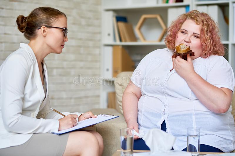 Obese Woman Consulting about Eating Disorder. Portrait of fat young women eating cupcakes during therapy session with female psychiatrist stock image