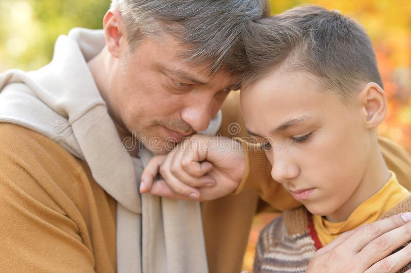 Portrait of father and boy in park stock images