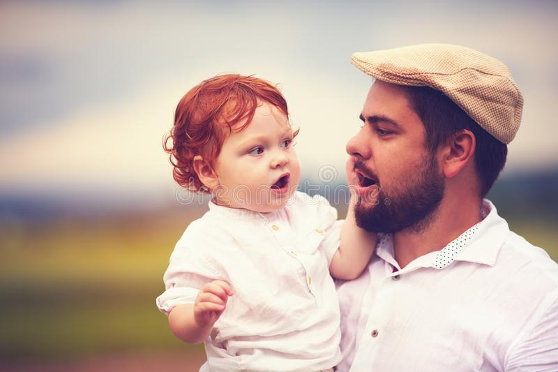 Portrait of father and cute redhead son in the countryside stock photo