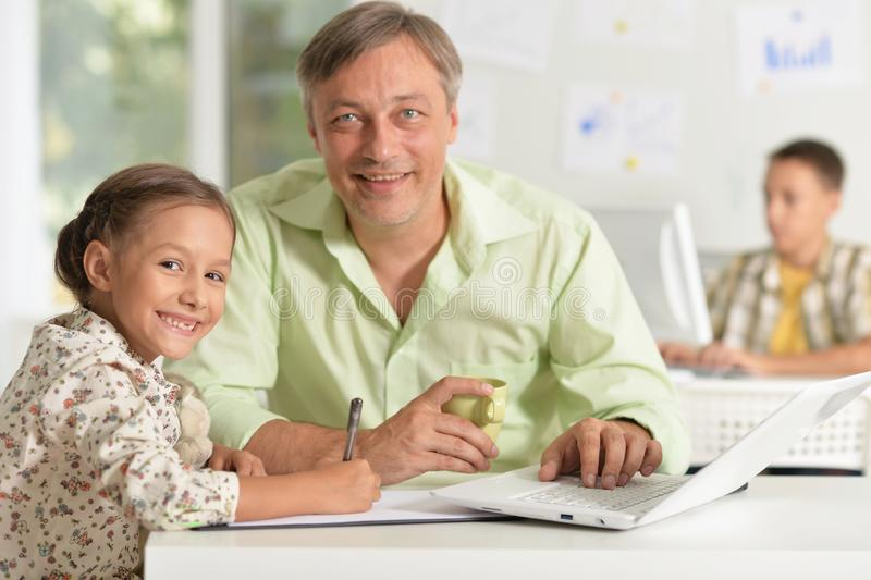 Portrait of father helping his daughter doing homework royalty free stock image
