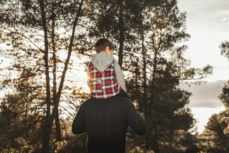 Portrait of a father with his son playing in the field. Child on his father`s shoulders. Portrait of a father with his cheerful son playing in the field. Child stock photo