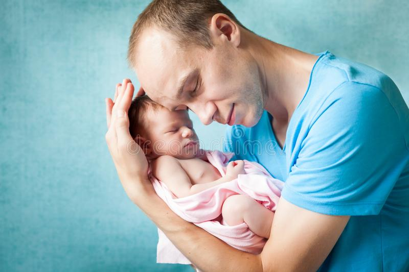 Portrait of father hugging his newborn baby. Portrait of happy young father hugging his adorable newborn baby. Concept of fatherhood, childcare royalty free stock photography