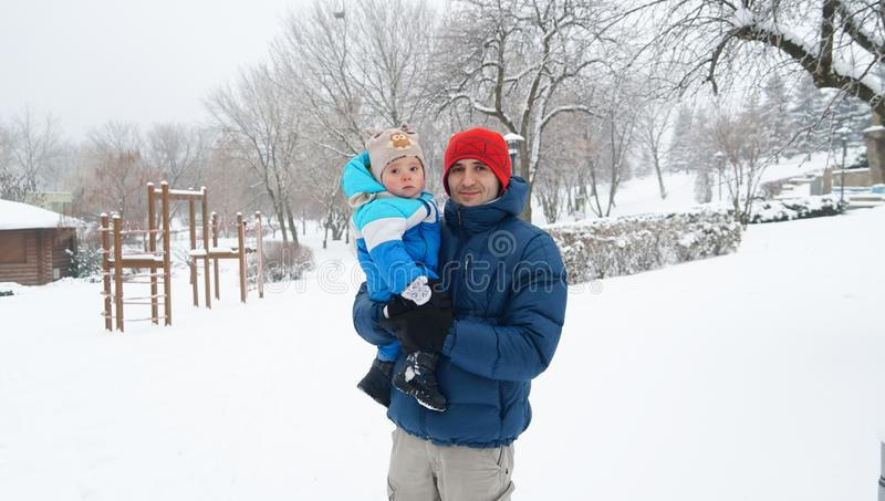 Father and boy on a cold winter day. Family concept.Daddy holds. A portrait of father and little boy on a cold winter day. Family concept. Daddy holds his cute royalty free stock images