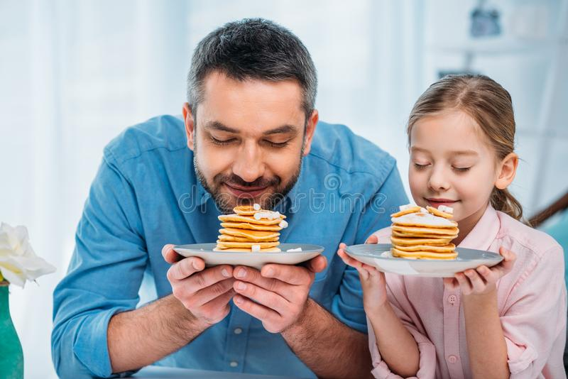 Portrait of father and little daughter sniffing pancakes for breakfast. At home royalty free stock images