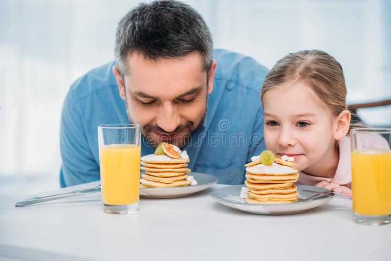 Portrait of father and little daughter sniffing pancakes for breakfast. At home stock photo