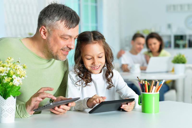 Portrait of father with little daughter using tablets stock photo