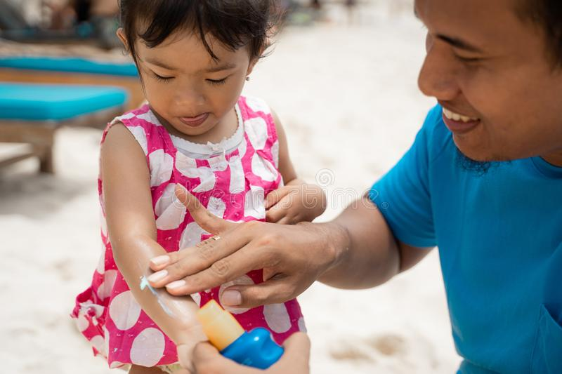 Portrait father rubbing a sunblock to daughter`s arm. Before playing on the beach at midday royalty free stock photography