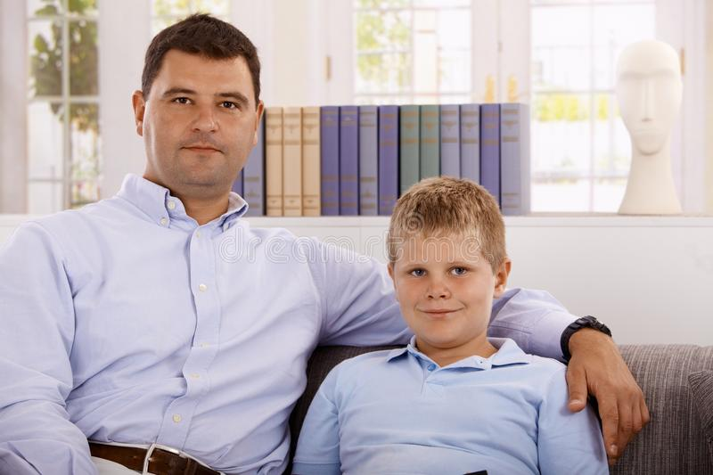 Portrait of father and son at home royalty free stock image