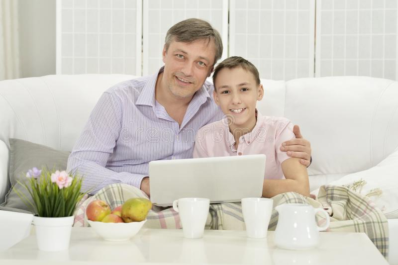 Portrait of father and son with laptop royalty free stock photos