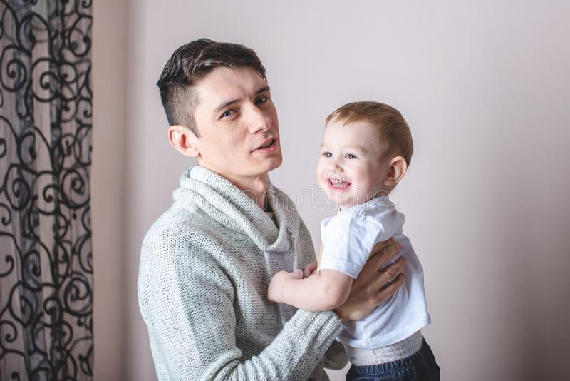Portrait of father and son`s baby. Fatherhood, love and protection of children. Family and continuity of generations. Portrait of father and son`s baby stock image