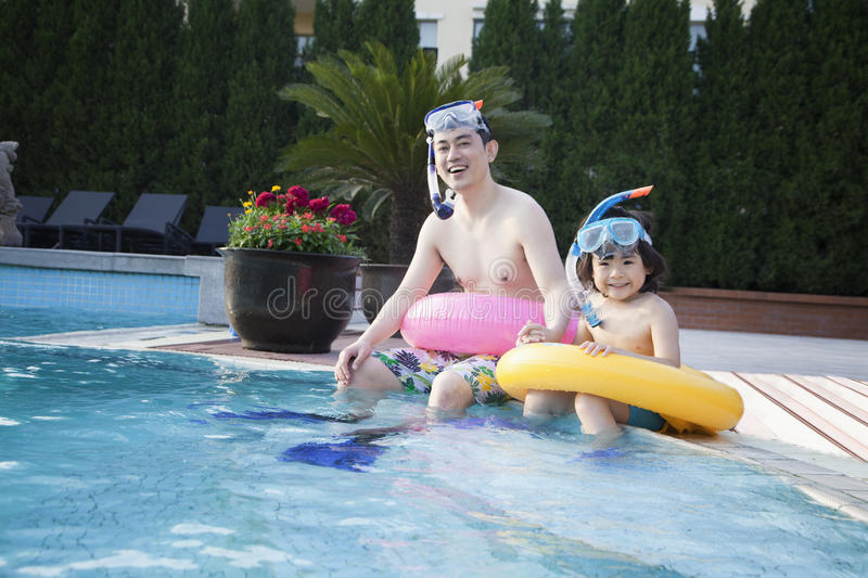 Portrait of father and son in snorkeling gear sitting by the edge of the pool stock images