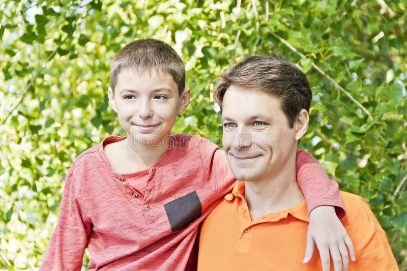 Father and teenager son together. Portrait of father and son in summer time royalty free stock photos