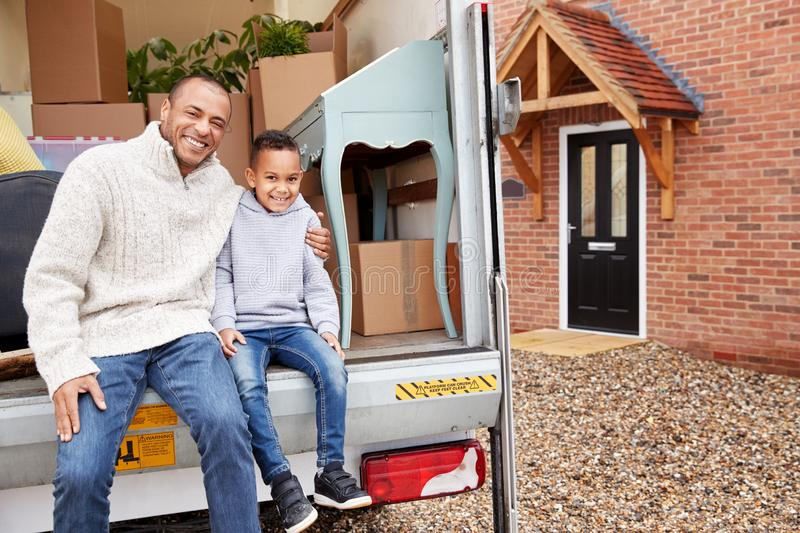 Portrait Of Father And Son Unloading Furniture From Removal Truck Into New Home stock image