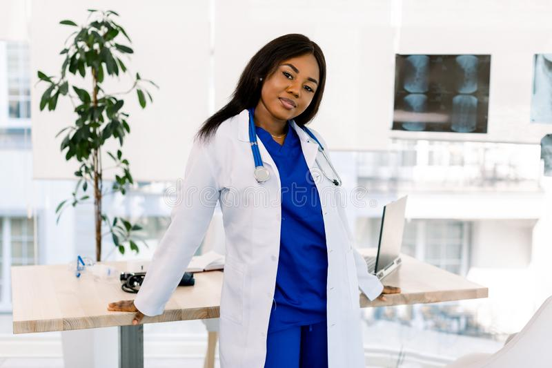 Portrait of a female African doctor in medical uniform posing in bright modern hospital royalty free stock photography