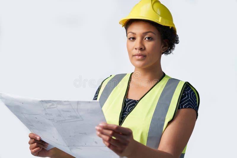 Studio Portrait Shot Of Female Architect Studying Plans Against White Background stock photo