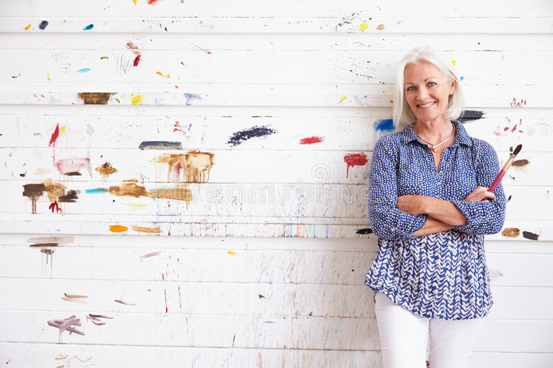 Portrait Of Female Artist Against Paint Covered Wall royalty free stock images
