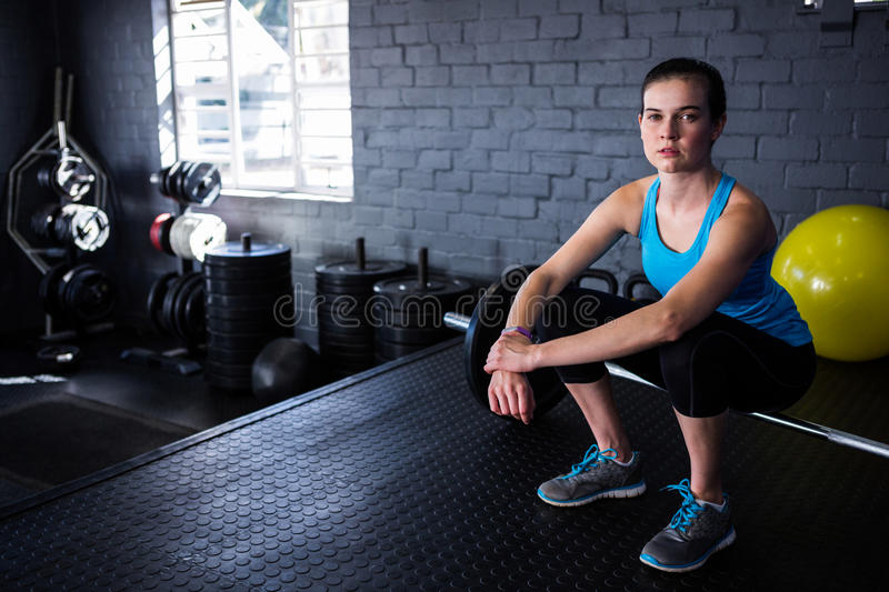 Portrait of female athlete sitting on barbell royalty free stock image