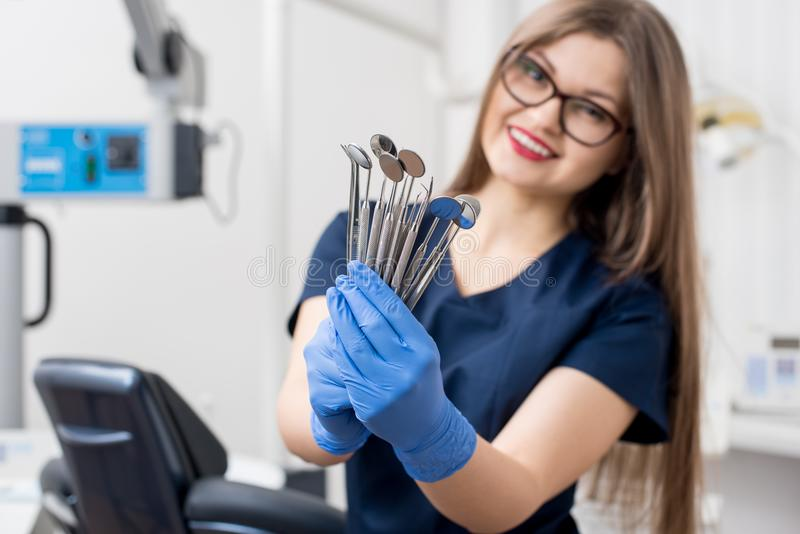 Portrait of female attractive dentist holding dental tools - at the modern dental office royalty free stock photo