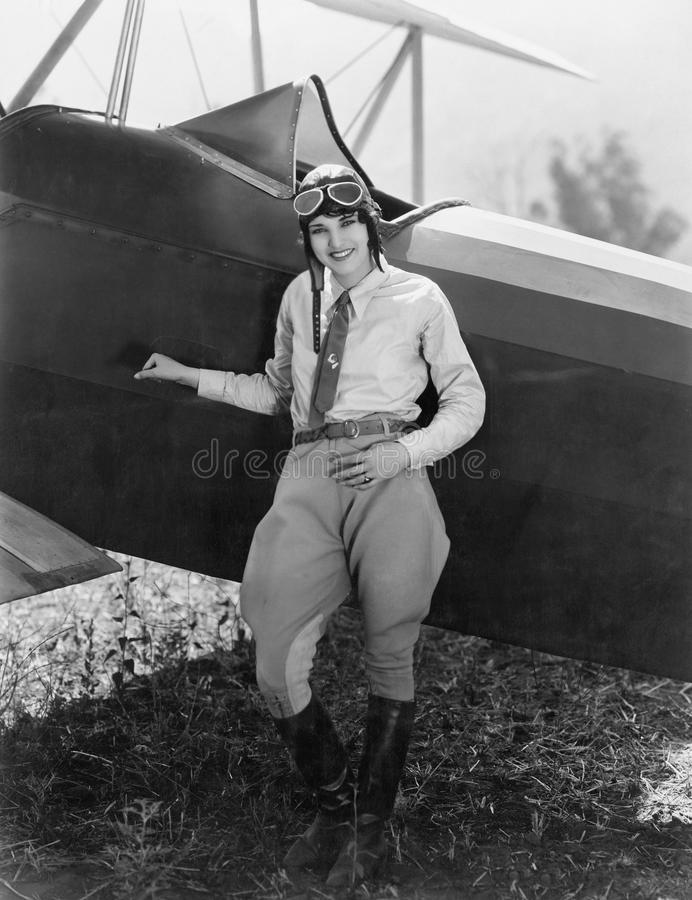 Portrait of female aviator with plane. (All persons depicted are no longer living and no estate exists. Supplier grants that there will be no model release stock image