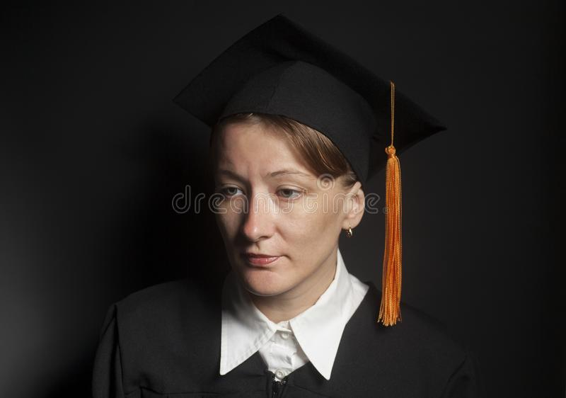 Portrait of Female bachelor in Black mantle and Graduation Cap. On a black background royalty free stock photography