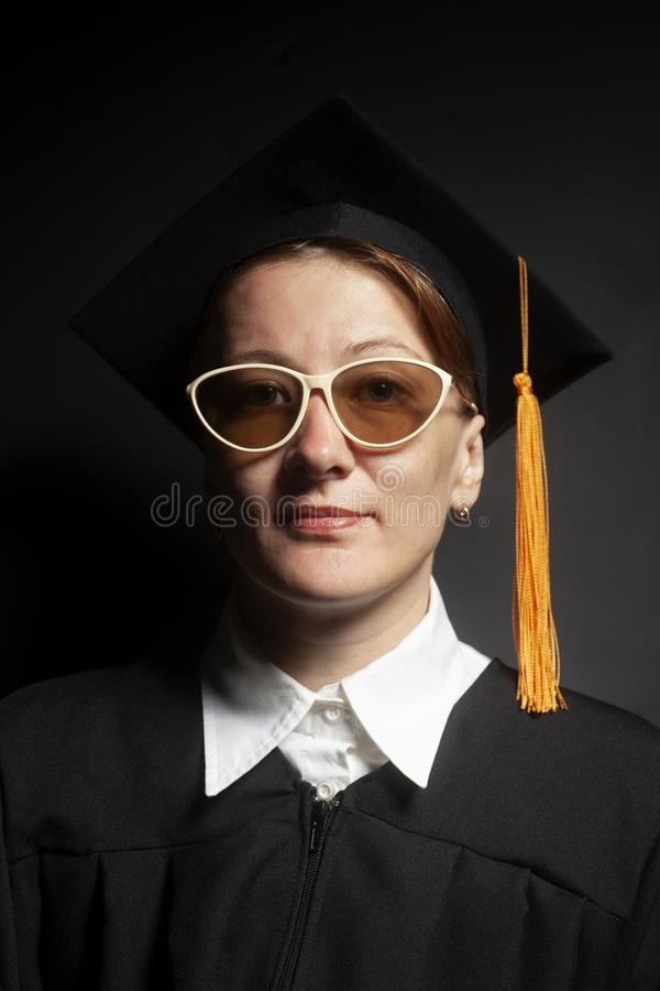 Portrait of Female bachelor in Black mantle and Graduation Cap with sunglasses. Portrait of Female bachelor in Black mantle and Graduation Cap on a black stock images
