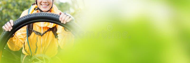 Portrait of female biker repairing mountain bike royalty free stock photography