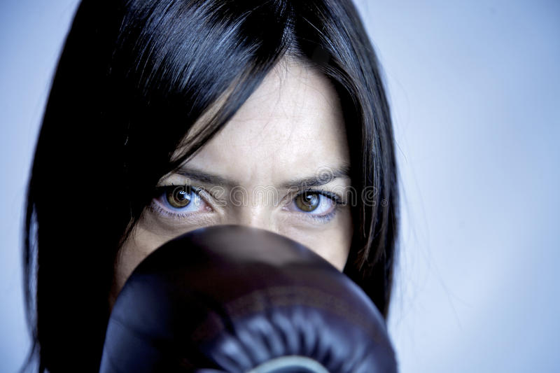 Portrait of female boxer. Strong woman behind boxer glove stock images