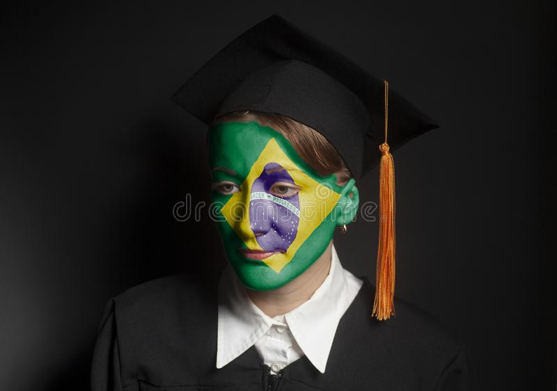 Portrait of Female brazilian bachelor with painted Flag of Brazil in Black mantle and Graduation Cap. On a black background royalty free stock images